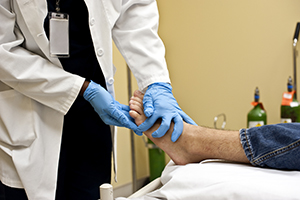 Chiropodist Checking The Bottom Of A Patient's Foot