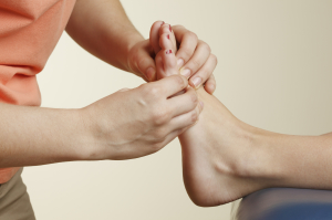 Chiropodist Massaging Patient's Foot