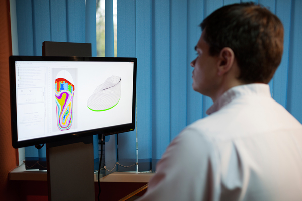A podiatrist creating custom orthotics to provide adequate arch support