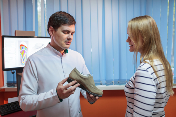 An orthopedic doctor giving demo to a patient with foot problems