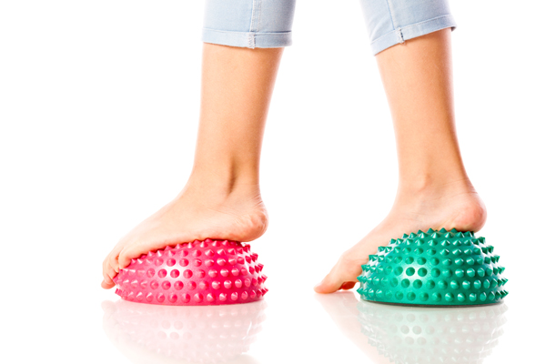 A girl balancing on soft-spike massage balls