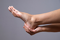 A woman holding her ankle in pain