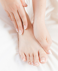 Woman massages own pedicured foot on white sheet