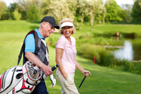 Senior Couple Walking On A Golf Course