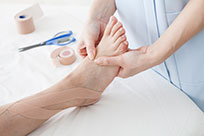 Practitioner who is taping aninjured Foot in Foot Clinic
